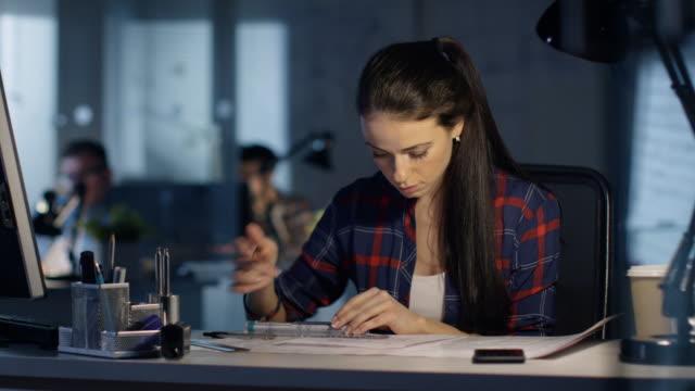 In-spät-Nacht-weibliche-Design-Engineer-Büroarbeiten-zu-Entwürfen-wit-dem-helfen-der-Ingenieur-Herrscher-in-regelmäßigen-Abständen-sie-berät-ihre-Computer-Tischlampe-leuchtet-ihr-und-Tabelle-Kolleginnen-und-Kollegen-arbeiten-im-Hintergrund-