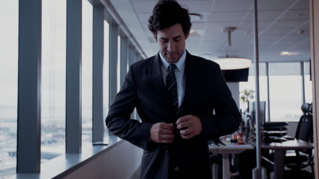 Young-businessman-buttoning-jacket