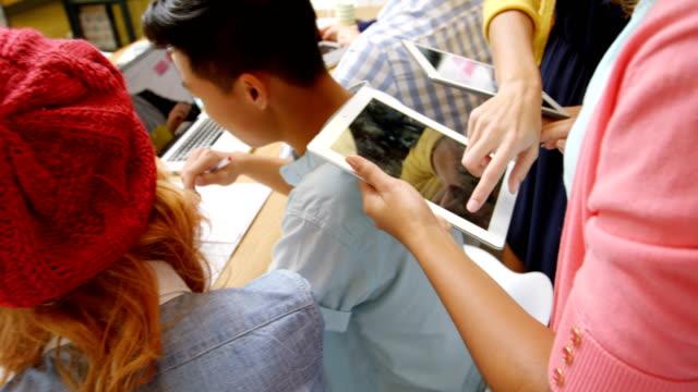 Ejecutivos-de-negocios-con-ordenador-portátil-y-tableta-digital-en-reunión
