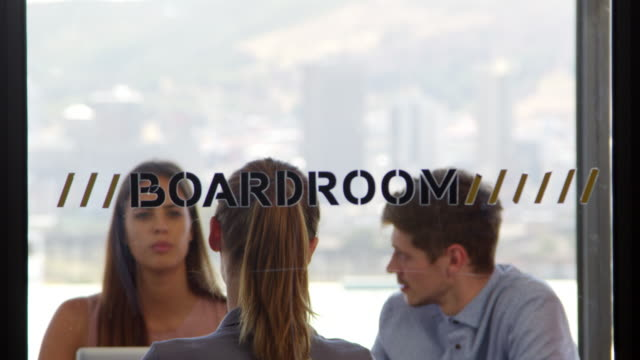 Three-young-colleagues-in-discussion-in-a-boardroom