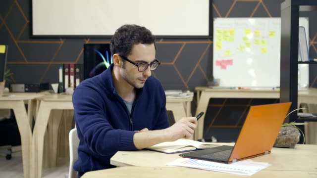 Creative-man-in-glasses-using-laptop-at-workplace