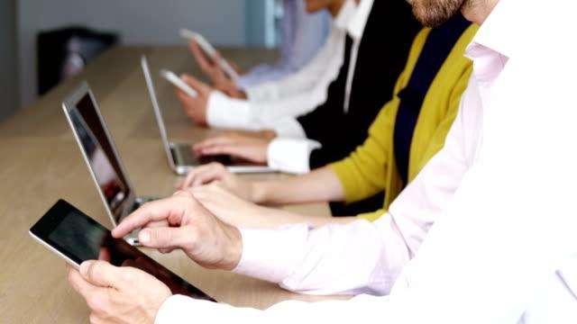 Equipo-de-negocios-usando-la-tableta-digital-y-portátil-en-la-sala