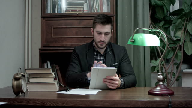 Young-man-sitting-at-desk-with-books-using-digital-tablet-in-home-room-office