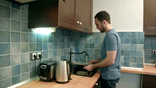 Young-man-washing-dishes-in-the-kitchen-at-home