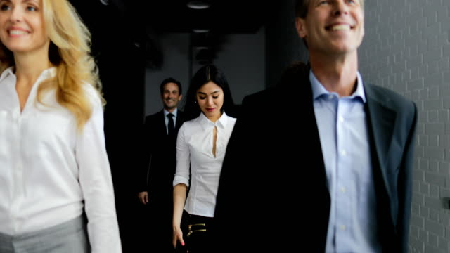 Equipo-de-gente-de-negocios-caminar-en-la-oficina-mientras-la-respuesta-empresaria-asiática-llamada
