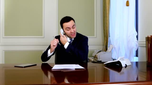 Hombre-de-negocios-enojado-tiene-una-conversación-caliente-con-alguien-en-el-teléfono-fijo
