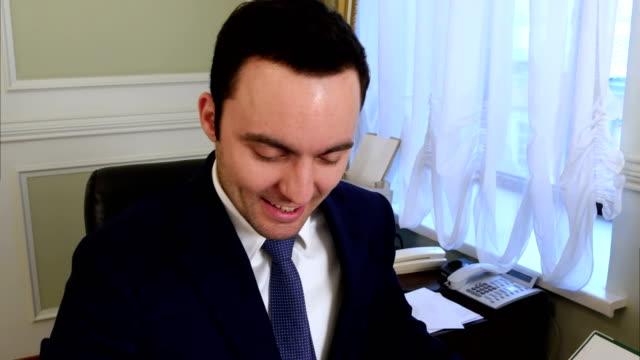Retrato-de-feliz-joven-empresario-leer-documentos-en-el-escritorio-en-la-oficina-y-sonriendo