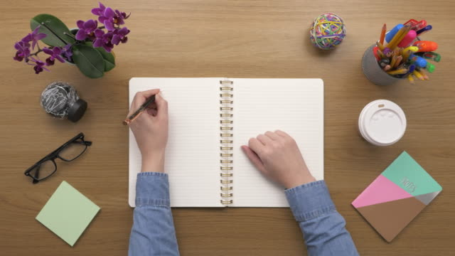 Overhead-Top-View-Of-woman-Making-To-Do-List-In-Diary