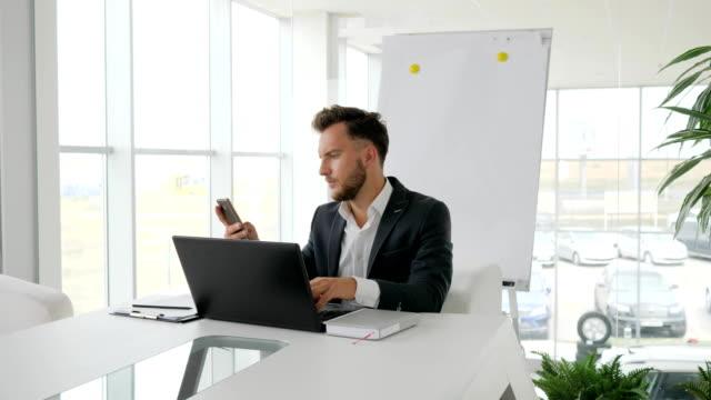 empresario-serio-funciona-en-el-portátil-a-Internet-en-sala-de-juntas-la-charla-de-ejecutivo-de-negocios-en-móvil-en-el-lugar-de-trabajo
