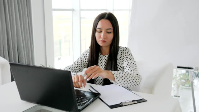 secretary-crumples-documents-beautiful-girl-manager-prints-text-on-laptop-at-desk-in-white-office-financial-crisis