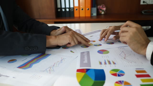 Businessman-examining-graphs-with-other-working-people-