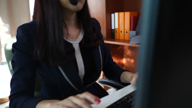 Businesswoman-sitting-by-the-computer-in-headphone-in-office-Call-center