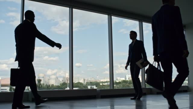 Gente-de-negocios-caminar-en-edificio-de-oficinas-con-ventanas-panorámicas