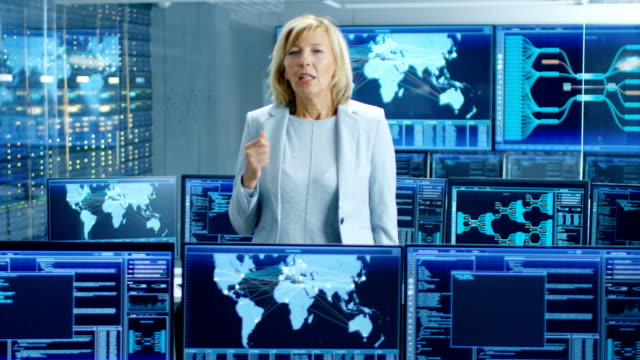 In-the-System-Control-Room-Female-Chief-Engineer-Describes-Her-Project-Talking-into-the-Camera-In-the-Background-Multiple-Screens-Showing-Interactive-Data-