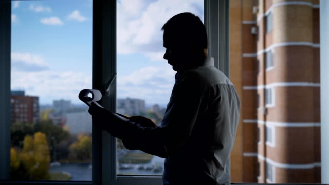 concentrated-businessman-is-reading-a-contract-on-a-paper-sheets-standing-in-front-of-window-in-his-office-in-autumn-day