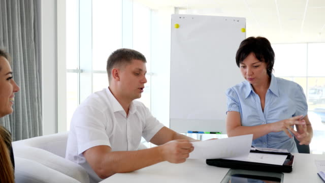corporate-executive-holding-meeting-with-team-of-collaborators-at-table-in-modern-office