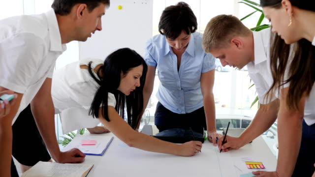 business-group-beside-desk-discussing-ideas-business-development-in-office