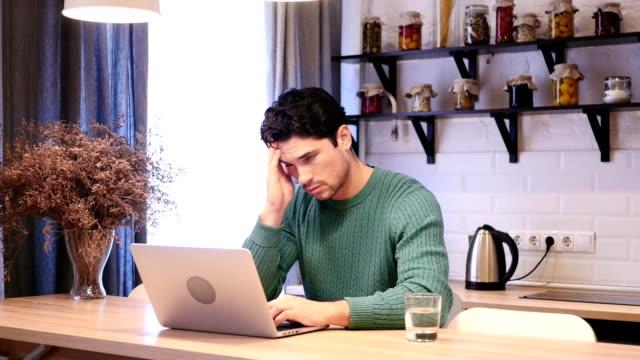 Dolor-de-cabeza-hombre-cansado-frustrado-trabajando-en-ordenador-portátil-en-la-cocina
