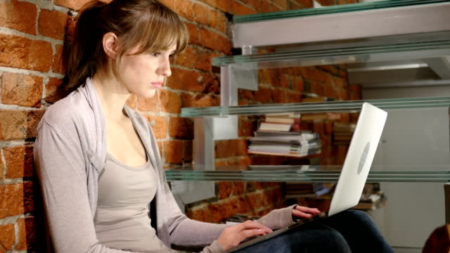 Joven-mujer-molesta-por-pérdida-mientras-trabajaba-en-la-computadora-portátil