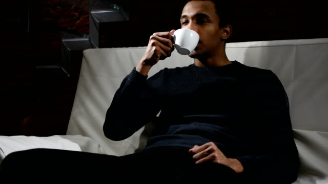Pensive-African-Man-Drinking-Coffee-from-Cup-Loft-interior