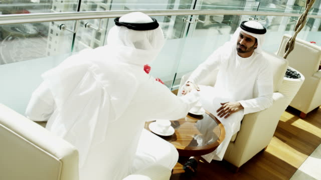 Emirates-businessmen-traditional-dress-handshake-downtown-city-office