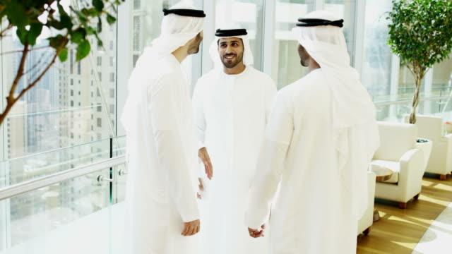 Dubai-Arab-businessmen-in-national-dress-meeting-downtown