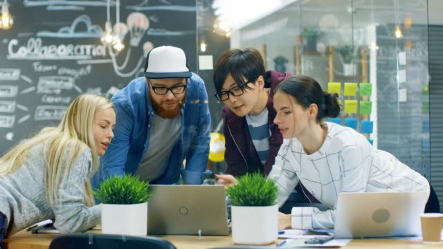 Diverse-Team-of-Young-Women-and-Men-Developers-Have-Team-Meeting-Using-Laptop-Beautiful-Young-People-in-Bright-Modern-Office-Environment-