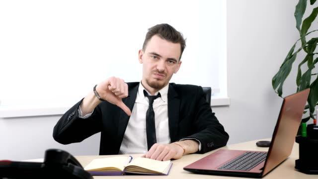 Joven-empresario-en-traje-sentado-en-oficina-y-mostrando-los-pulgares-para-arriba-firman-60-fps