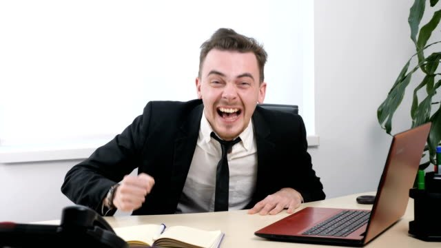 Young-businessman-in-suit-sitting-in-office-and-laughing-hysterically-60-fps