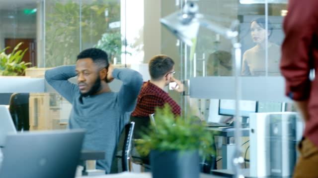 Internationales-Büro-schöne-Hispanic-Frau-arbeiten-an-ihrem-Schreibtisch-auf-einem-Laptop-in-den-Hintergrund-vielfältige-Gruppe-von-kreativen-Kollegen-arbeiten-beschäftigt-