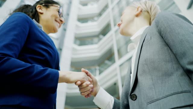 Tiro-de-ángulo-bajo-de-empresaria-estrecharme-la-mano-y-hablando-con-el-colega-de-negocios-mujer-traje-en-hall-del-edificio-de-oficinas-moderno
