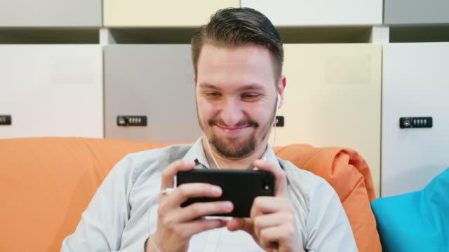 Mann-ansehen-von-Videos-auf-dem-Smartphone-im-Innenbereich