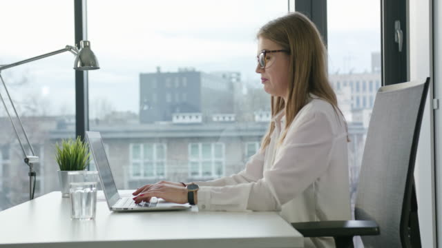 Bisinesswoman-Sitting-and-Using-a-Laptop-Indoors