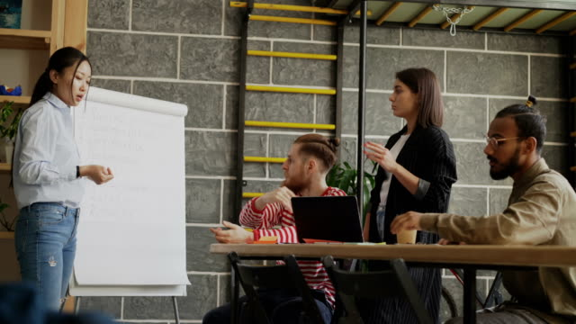 Cheerful-asian-girl-explaining-start-up-business-plan-on-flipchart-to-colleagues-in-modern-loft-office