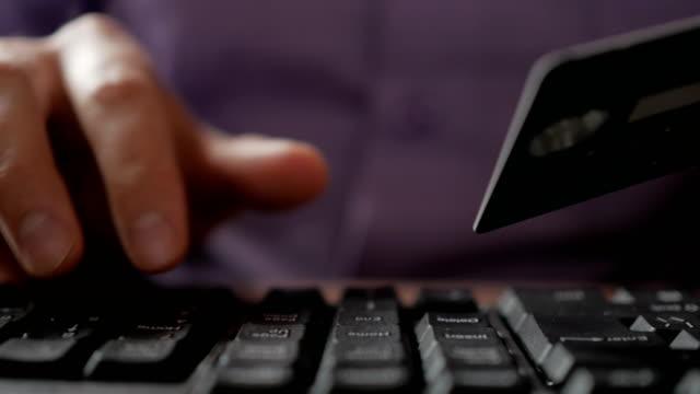 Pagando-con-una-tarjeta-de-crédito-en-línea-compras-Manos-masculinas-con-tarjeta-de-crédito-en-compras-a-través-de-Internet-Teclado-de-la-computadora-Closeup-Hombre-de-negocios-hizo-un-pago-electrónico-
