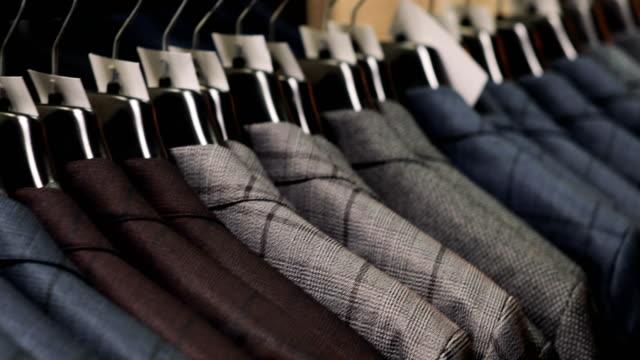 Man-choosing-a-suit-at-tailor-s-shop