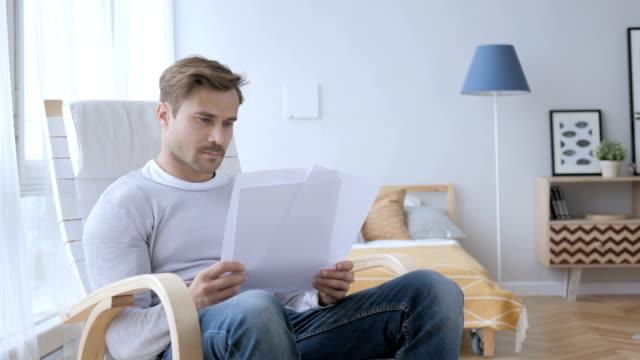 Documentos-de-lectura-de-adultos-hombre-sentado-en-silla-relax