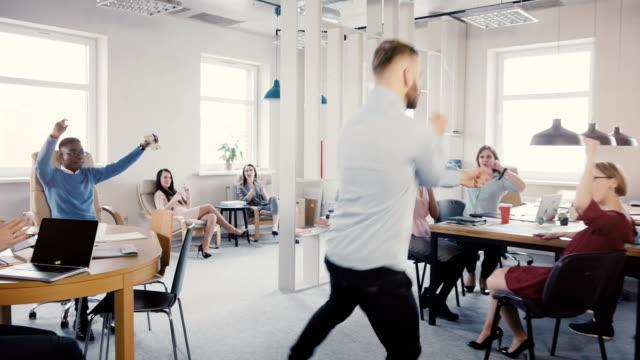 Cámara-sigue-a-pie-feliz-empresario-en-oficina-haciendo-baile-divertida-celebración-Trabajadores-multiétnicos-ríen-y-aplauden-4-K