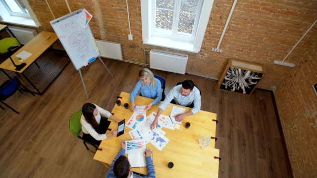 Business-meeting-at-loft-shared-space-Team-talking-woman-manager-giving-direction-to-people-Top-view-