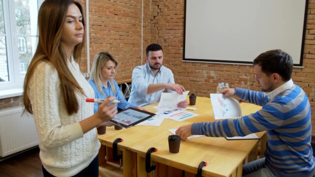 Creative-Business-team-meeting-woman-manager-presenting-financial-data-to-shareholders-using-digital-tablet-in-casual-modern-office-boardroom-with-natural-light