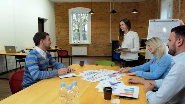 Kreative-Business-Team-treffen-Frau-Manager-präsentiert-Finanzdaten-an-die-Aktionäre-mit-digital-Tablette-in-lässig-moderne-Büro-Tagungsraum-mit-Tageslicht