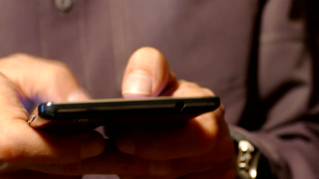 Un-hombre-escribiendo-en-un-smartphone-de-pantalla-táctil