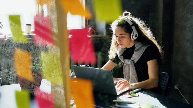 Attractive-female-student-is-listening-to-music-with-headphones-dancing-and-singing-while-working-with-laptop-computer-Glassboard-with-bright-colored-stickers-in-foreground-