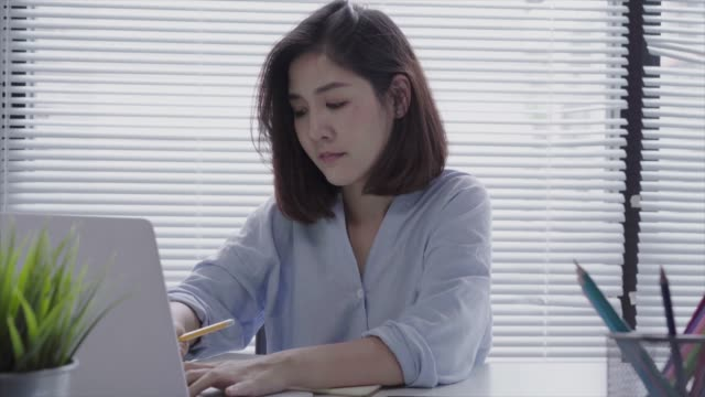 Beautiful-young-smiling-asian-woman-working-on-laptop-while-sitting-in-a-living-room-at-home-Asian-business-woman-working-in-her-home-office-Enjoying-time-at-home-