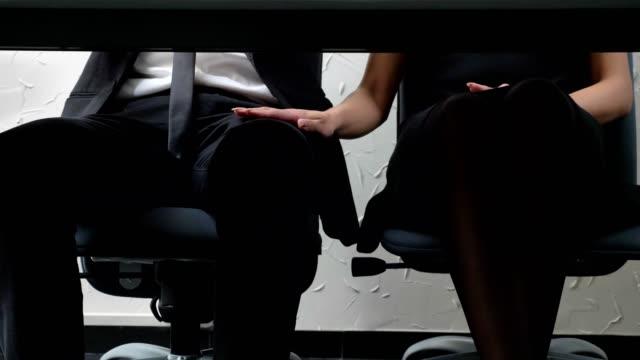 Tiro-debajo-de-la-mesa-jefe-de-la-mujer-joven-sentada-al-lado-de-su-empleado-y-toca-su-pierna-ligones-concepto-acoso-50-fps