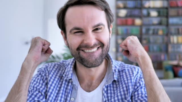 Hombre-celebra-éxito-Win-Gesture-en-oficinas-4k-alta-calidad