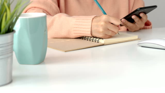 Young-asian-women-business-owners-using-app-smartphone-and-take-notes-in-office-