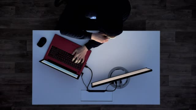 Young-man-in-black-hoodie-drinking-coffee-and-typing-on-laptop-during-night-sitting-behind-white-desk-top-shot