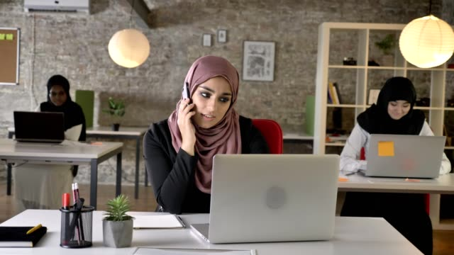 Three-young-muslim-womans-in-hijab-sitting-and-working-in-modern-office-beautiful-muslim-woman-talking-on-phone-smiling