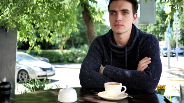 Young-Man-Sitting-in-Cafe-Terrace